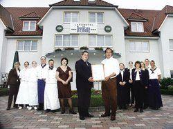 Hotelier Uwe Heymann (vorne rechts) nimmt von Olaf Seiche die Zertifizierungsurkunde entgegen. <tbs Name=