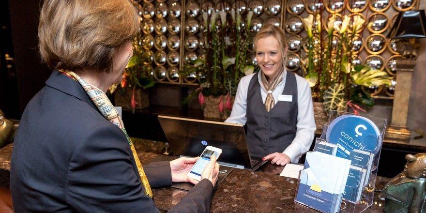 Live-Test: Kölns Oberbürgermeisterin Henriette Reker (links) checkte über Conichi im Savoy Hotel ein