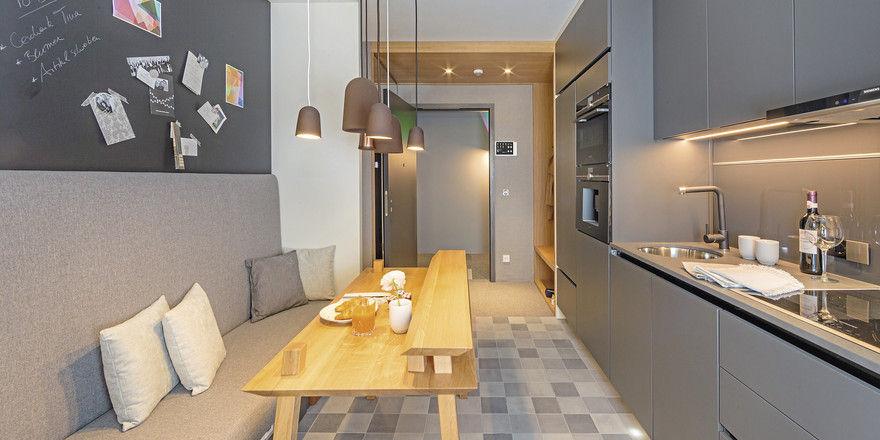 Multifunktionaler Küchenbereich: Ess- und Arbeitstisch, Sitzbank mit Wachstumspotenzial und Licht aus Kaffeesatz-Lampen.