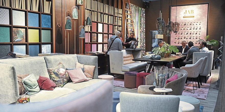 Ganz wohnlich: In Sitzmöbeln sollten Gäste sich wohlfühlen, weiche Polster sind dabei gefragt. Auf dem Tisch wird es zunehmend rustikal. Hartporzellan in Keramikoptik garantiert die Spülmaschinentauglichkeit.