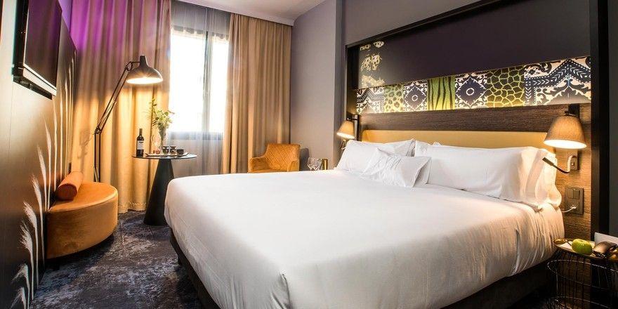Grau mit goldenen Akzenten kombiniert: Eines der Hotelzimmer im NYX Hotel in Madrid