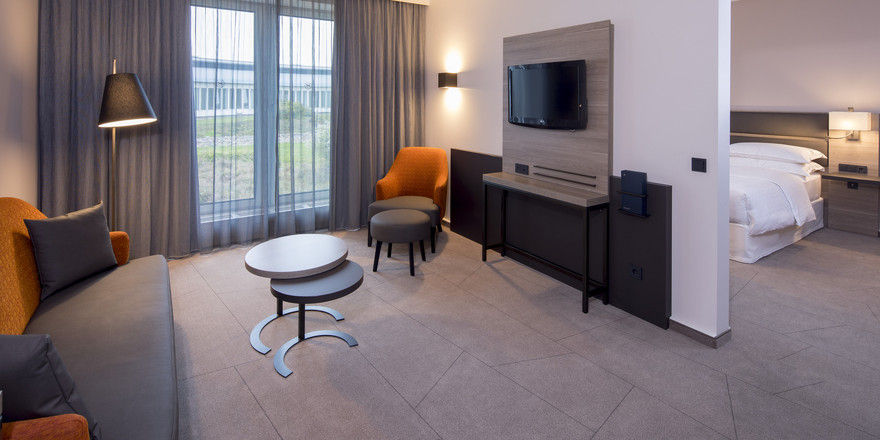 Grautöne kombiniert mit Orange: Der Wohnbereich der King-Junior-Suite