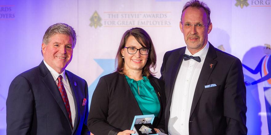 Feierliche Übergabe: (v.l.) Ralf Müller und Rebekka Brox von den Johannesbad Hotels erhalten den Preis in New York von Michael Gallagher, Präsident der Stevie Awards