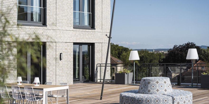 Die Dachterrasse: Der graue Klinkerbau steht für Klarheit, das Sofa ist verspieltes Element.
