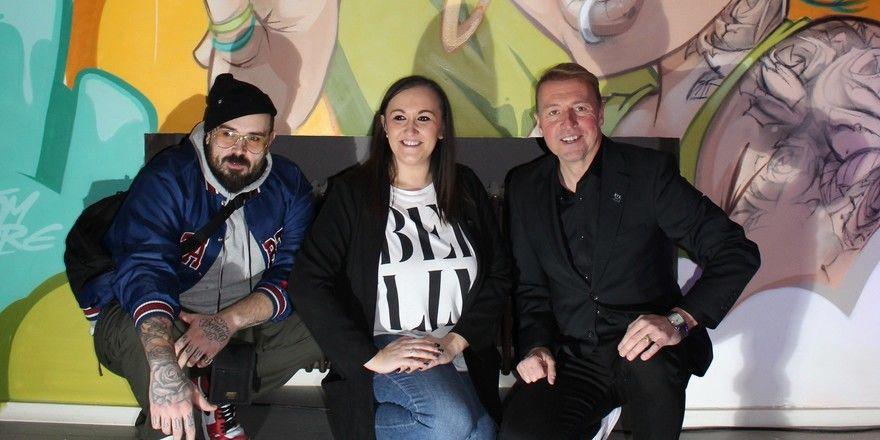 Kunst spielt in den NYX-Hotels eine große Rolle: (von rechts) Jan Heringa, Brand Manager NYX-Hotels, Kristina Pekas, Operations Manager Mannheim und der Mannheimer Künstler Hombre Suk vor seinem Graffiti-Kunstwerk