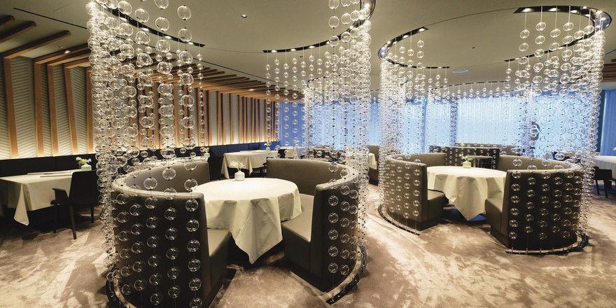 Tannenholz an den Wänden, Glaskugeln als Raumteiler: So präsentiert sich das Restaurant Ösch Noir den Gästen. Am Chefs Table (rechts) können sich Gourmets ganz auf die Kreationen von Spitzenkoch Manuel Ulrich konzentrieren.
