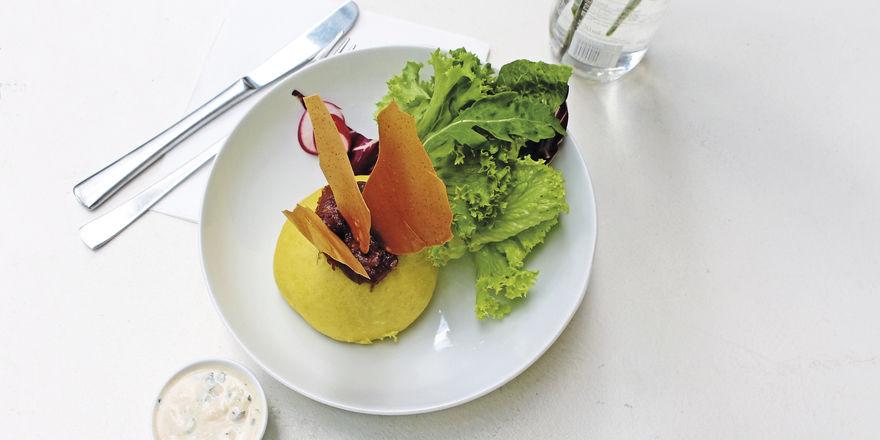 Österreich trifft Indien: Germknödel mit Dal-Füllung, Dattel-Chutney, Papadam, Tomaten und einem Koriander-Joghurt-Dip.