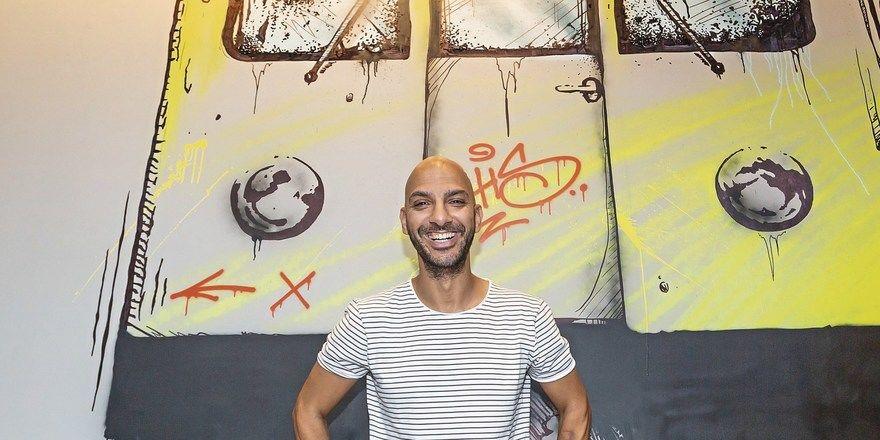 Inspiriert von der nahen East Side Gallery: Nizar Rokbani vor Graffiti im Hotel.