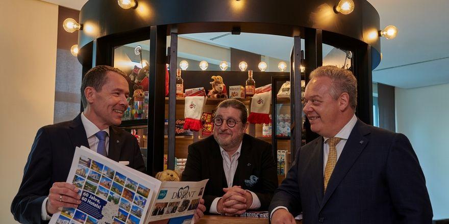"""Dorint hoch drei: Dirk Iserlohe (CEO Honestis AG, Mitte), Karl-Heinz Pawlizki (CEO Dorint GmbH, links) und Jörg T. Böckeler (COO Dorint GmbH) feiern 60 Jahre Dorint an einem Kölschen """"Büdchen"""""""
