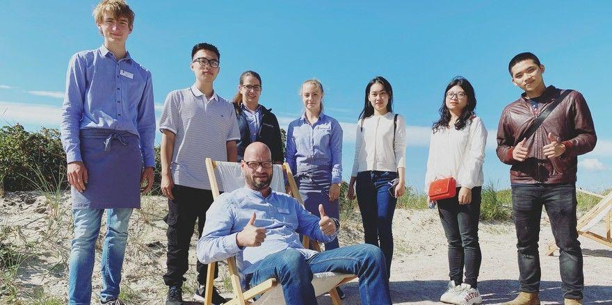 Erstmals auch auf Nachwuchs aus Vietnam: Die sieben neuen Azubis im Strandgut Resort St. Peter-Ording mit Matthias Reisewitz, stellvertretender Hotelleiter F&B (vorn)