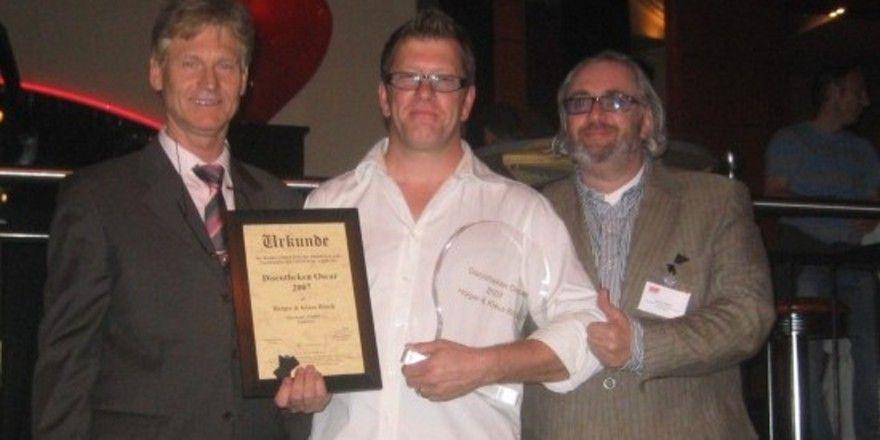 Holger Bösch(M.) nimmt den begehrten Branchen-Award von BDT-Präsident Henning Franz (l.) und BDT-Vizepräsident Ulrich Weber (r.)