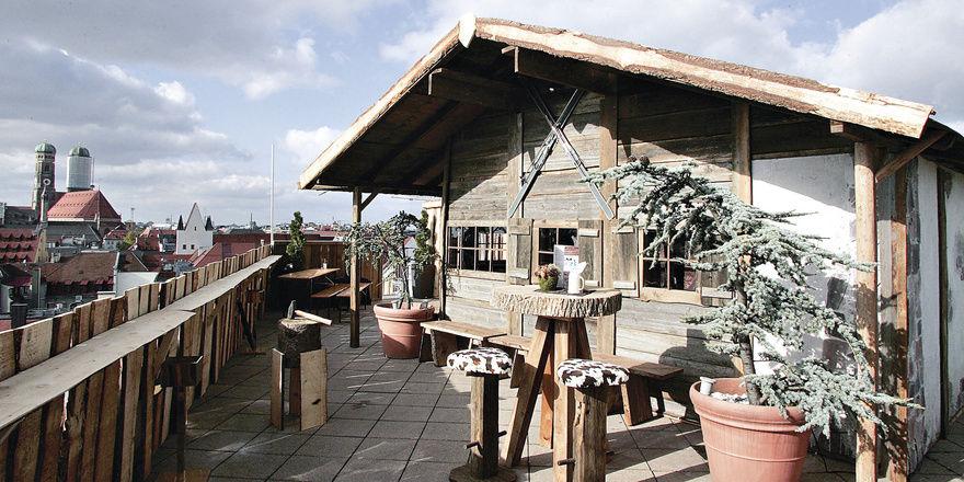 Alpine Gemütlichkeit: (von oben) Die Hütte des Leonardo Royal Hotels Munich von außen und innen. Von der Alm auf dem Dach des Mandarin Oriental haben die Gäste einen feinen Blick über die Stadt
