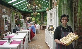 Bekannt für ihre Kuchen: Beate Palmen im viktorianisch angehauchten Wintergarten ihres Cafés