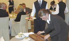 Praxisteil: Finalteilnehmer beim Filetieren am Tisch.