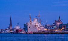 Blickfang: Mit seiner Silhouette aus Kirchtürmen und Schiffsmasten ist der Stadthafen Rostock ein Anziehungspunkt für Besucher.