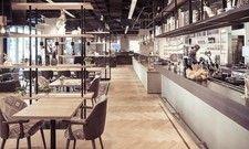 Herzstück der Beckeria: Ein heller Verkaufstresen aus matt grauem Sichtbeton mit einer Arbeits- und Präsentationsfläche aus Naturstein.