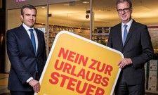 """Norbert Fiebig vom Deutschen Reiseverband und RDA-Präsident Benedikt Esserpräsentieren das Logo zur Initiative """"Nein zur Urlaubssteuer""""."""