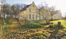 Zauberhaftes Grundstück: Das Wildkräuterhotel in gelbem Farbton und mit kleinem Garten.