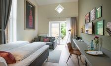 Klare Linien kombiniert mit Weingläsern, Weinflaschen und mehr: Ein Hotelzimmer des Themenhotels Weinbek