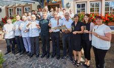 Sie haben allen Grund zu feiern: Die Burgschänke-Betreiberfamilie Sievers (Mitte) und ihre Mitarbeiter