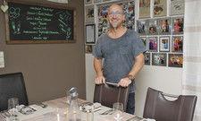 Startklar: Christian Krüger am eingedeckten Tisch. In Hintergrund Fotos mit bekannten Köchen.
