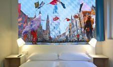 Themendesign mit regionalem Bezug im B&B Hotel Landshut: Wandtafeln über den Betten bilden die Landshuter Hochzeit ab