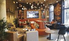 Gemütliches Ambiente: Die Wohnzimmer-Lobby im neuen Düsseldorfer Moxy. Die Henkel-Marke Schwarzkopf ist als Wanddeko vertreten.