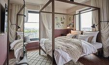 Für Romantiker: Im französischen Zimmer bedeckt ein Überwurf aus Leinen das Bett. Vor den Fenstern bauschen sich hellbeige Gardinen in Doppellage, die sich zum Verdunkeln eignen