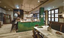 Blickfang: Herzstück des Raums ist der große Bar-Tresen mit seinem Schankbalken aus Kupfer und grüner Ziegelverkleidung