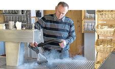 Praxiseinsatz im Ochs am Berg: Gastronom Rupert Kimpfler zeigt, wie das Dampfsaugsystem Blue Evolution XL+ von Beam mit Fettresten Schluss macht.