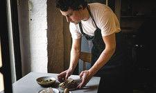 Wie ein Kunstwerk: Vadim Otto Ursus beim Anrichten von Sauerteigbrot mit Koji-Butter, gesalzenem Rückenspeck vom Mangalitza-Wollschwein aus Brandenburg mit Solei und fermentiertem Gemüse.