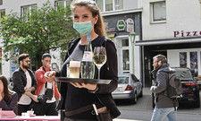 Herzlich Willkommen: Diese Servicemitarbeiterin versprüht trotz Mund-Nase-Schutz gute Laune.