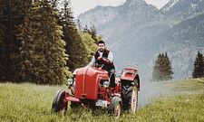 Kultiges Gefährt: Mit diesem roten Porsche-Traktor schickt Bernd Ebert, Chef des Pfrontener Hotels Schlossanger Alp, Männer auf Spritztour durchs Allgäu.