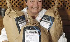 Hat gut lachen: Andrea Rüdell präsentiert drei Säcke der angeblich rebsortenreinen Holzkohle, um die sich ihr Aprilscherz drehte